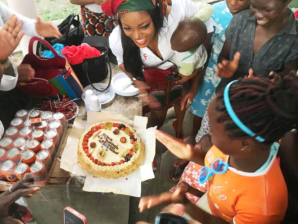 Willgrace Guety, coach Manager de Femmes Chics et Fabuleuses soufflant la bougie du 1er Anniversaire de l'association en compagnie des enfants du centre d'acceuil d'Angodje.